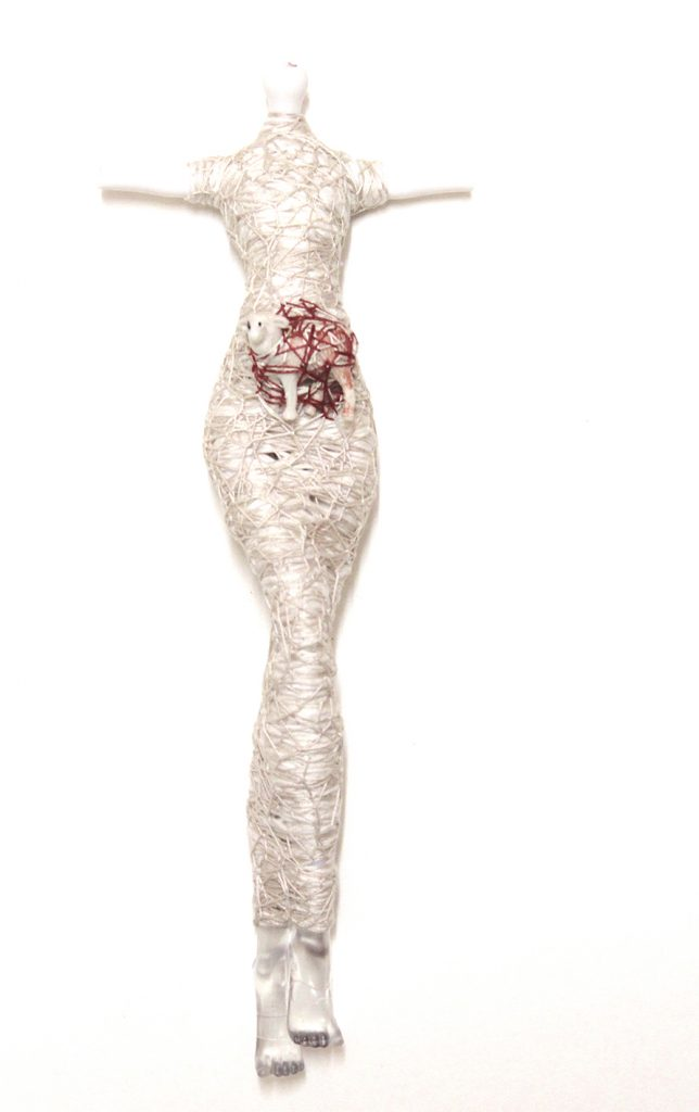 Doll without head or arms wrapped in thread