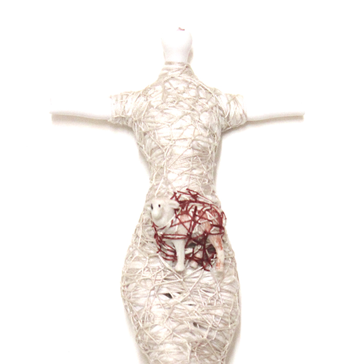 Toy lamb attached to doll torso by wrapped threads. Doll is also wrapped
