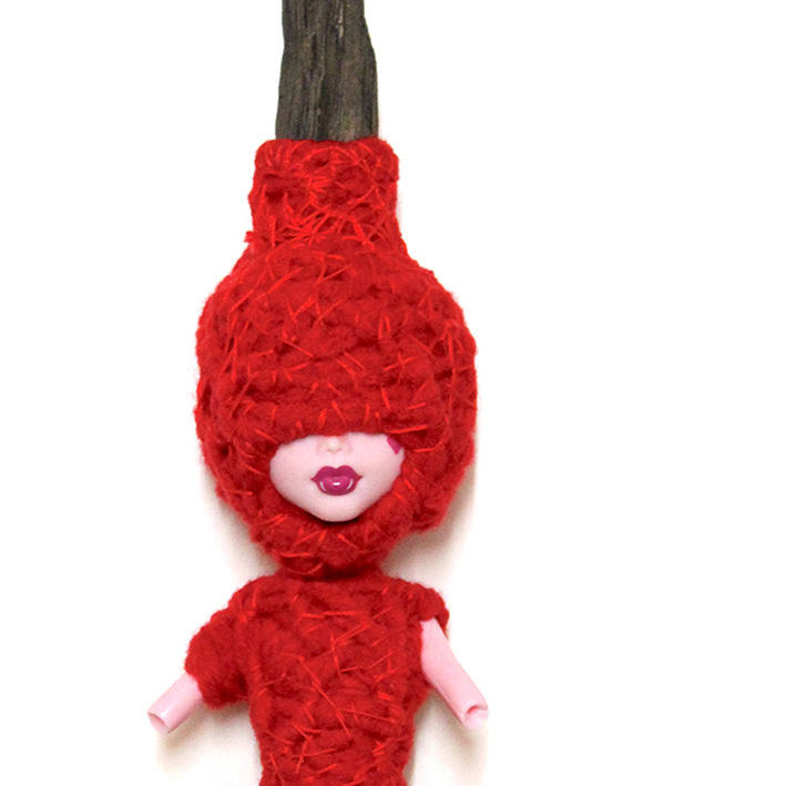 Doll with torso and most of face wrapped in red yarn