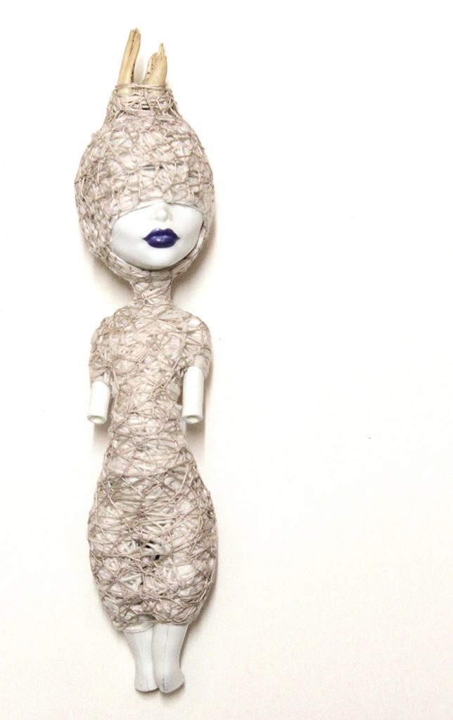 Doll without missing arms and legs wrapped in white thread, including most of face