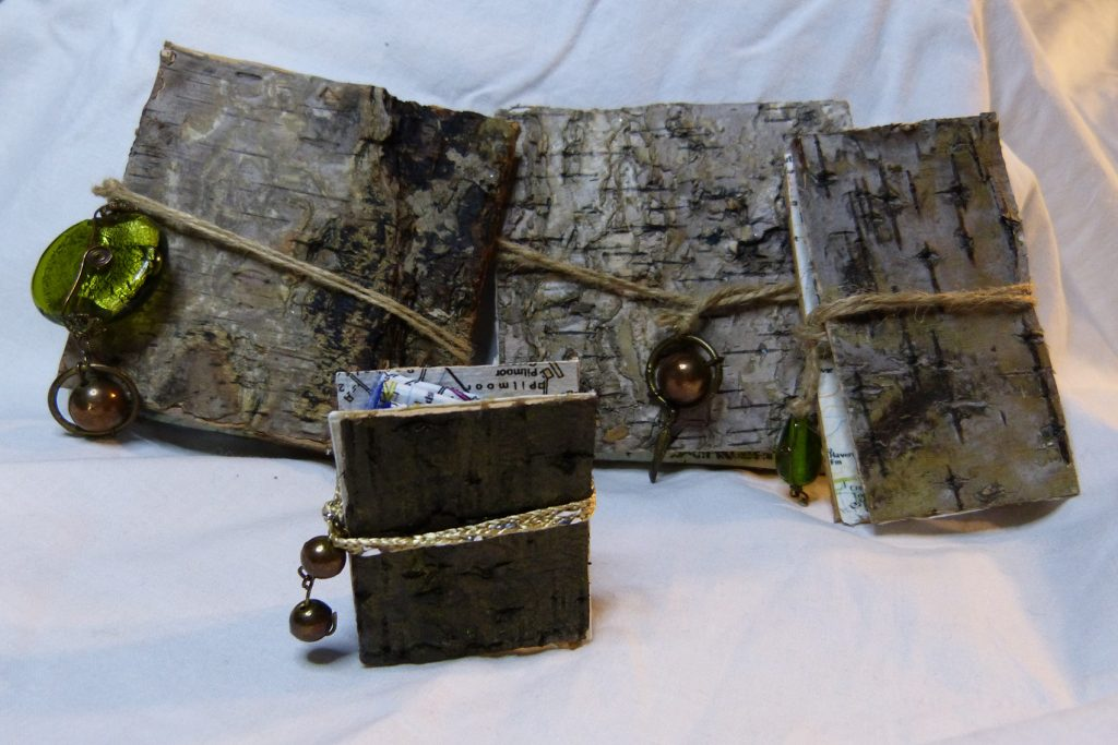 Three large and one small artists books, covered in birch bark and decorated with beads