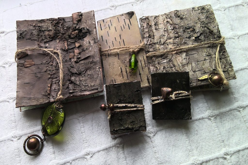 Three large and two small artists books, covered in birch bark and decorated with beads