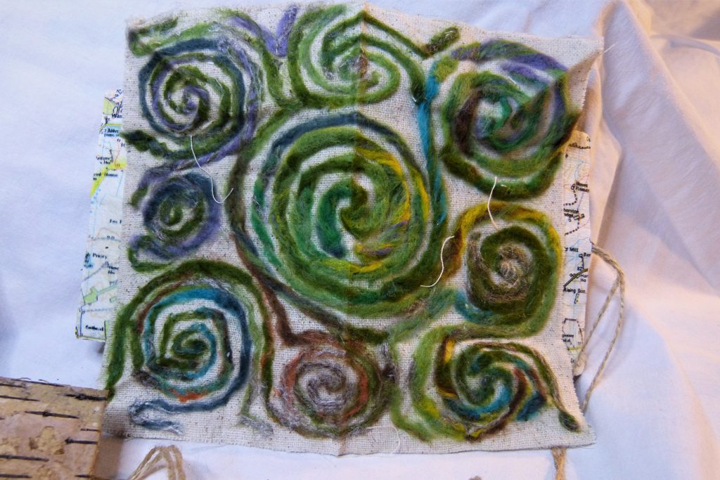Green wool spirals pattern on pages of open book