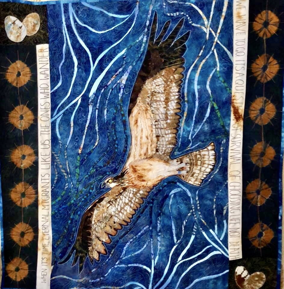 An osprey in flight across a sky of blue and white air currents. Borders down the side of this textile piece are repeated ti-dyed brown discs