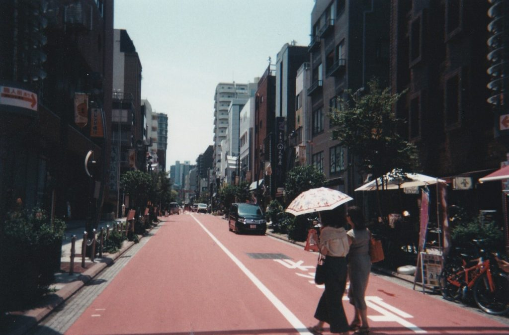 Photograph of Tokyo street. Two women walk away fromus into the road